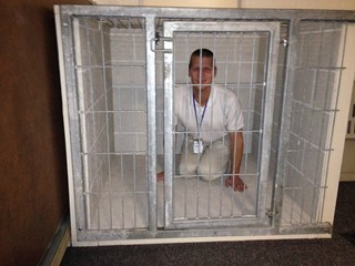 Wil kneels inside a current Leader Dog kennel cage.
